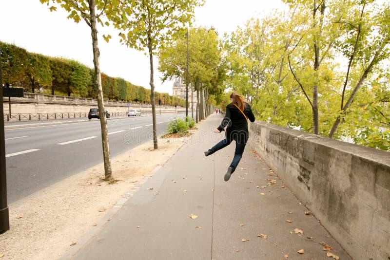 Calle de Autumn Parisian, una muchacha en una capa negra, tejanos y zapatillas de deporte en un salto foto de archivo libre de regalías