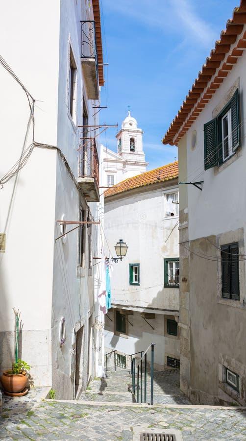 Calle de enrrollamiento estrecha típica en el distrito de Alfama, Lisboa, Portugal imagenes de archivo