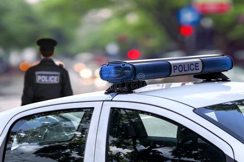 Calle de la conducción de automóviles del servicio de emergencia del oficial de policía en la ciudad imagenes de archivo