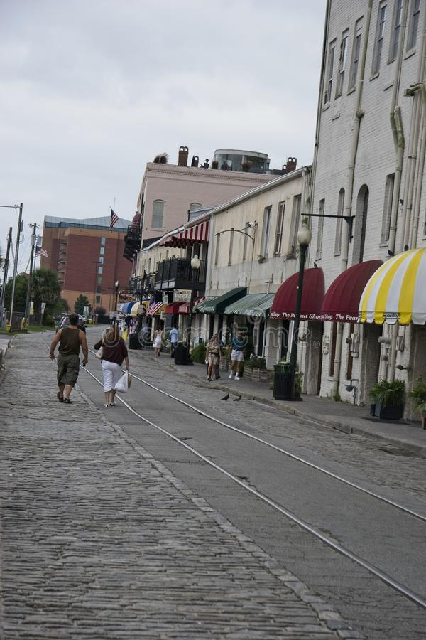 Calle de la piedra del adoquín con las pistas de ferrocarril viejas imagenes de archivo
