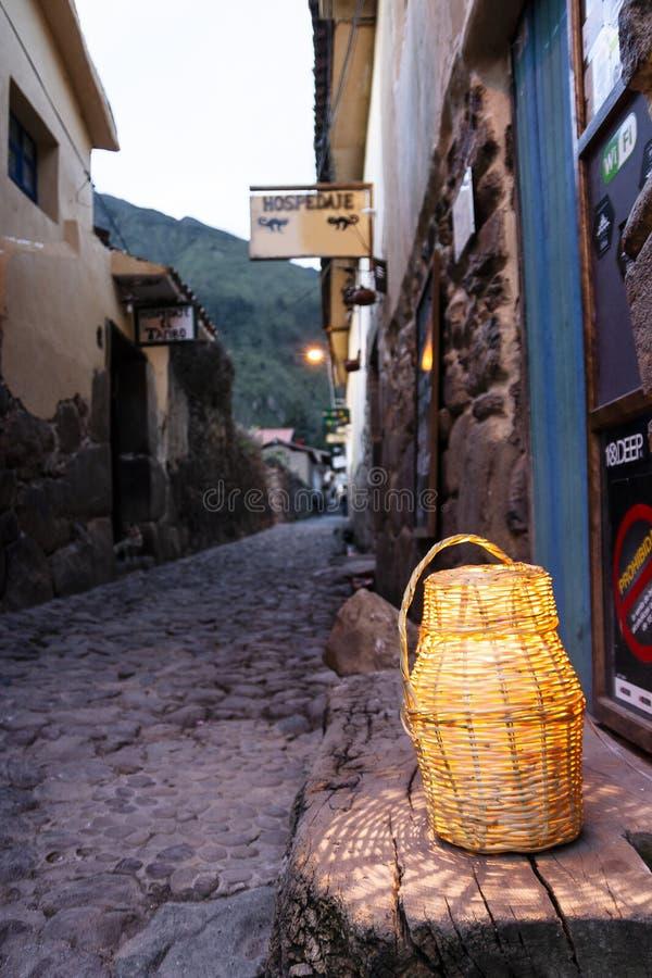 Calle de la piedra del adoquín con la linterna que se sienta en el soporte de madera imagenes de archivo