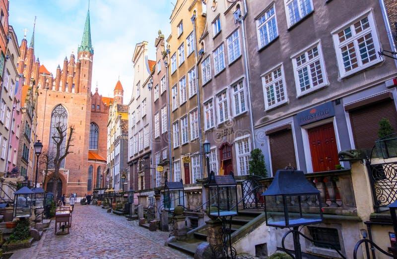 Calle de Mariacka con las fachadas coloridas de las casas de vivienda y de la iglesia g?tica del siglo XVI del ` s de St Mary, Gd imagen de archivo