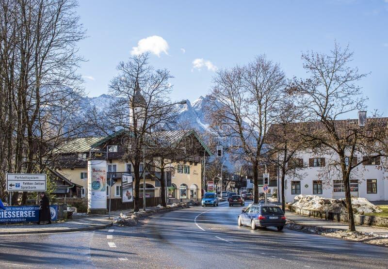 Calle de una pequeñas ciudad y estación de esquí alpinas con las casas, el camino y las montañas típicos imagen de archivo