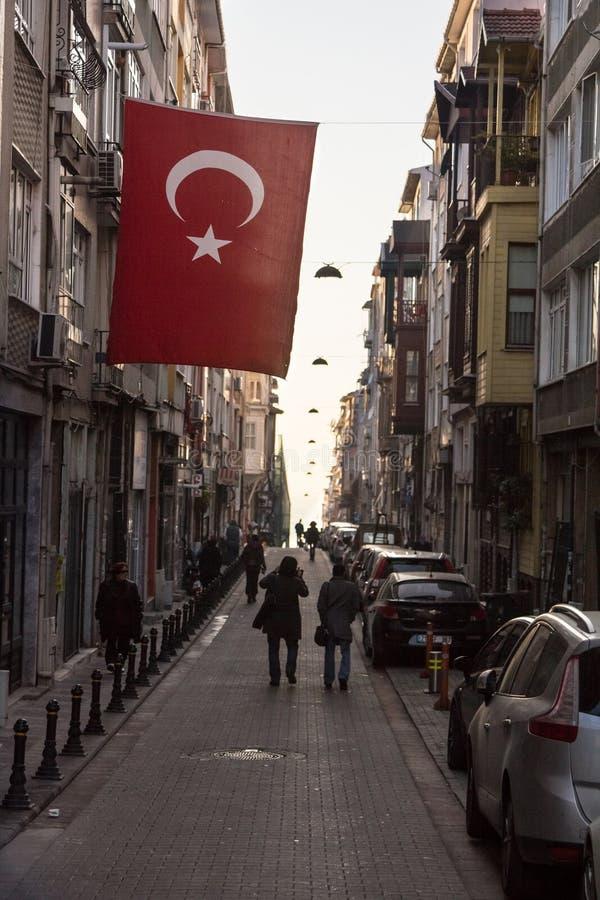 Calle del distrito Kadikoy en el lado asiático de Estambul, con una ejecución turca de la bandera, en la puesta del sol fotos de archivo