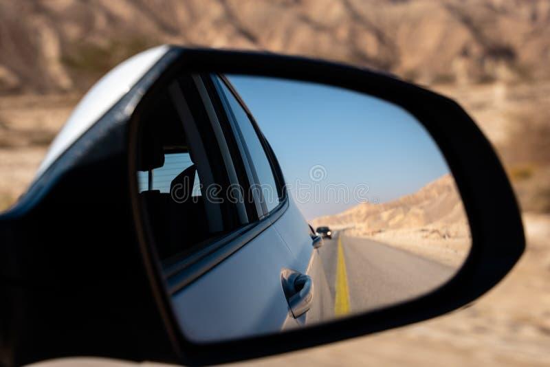 Calle, desierto y coche vistos del espejo retrovisor fotos de archivo