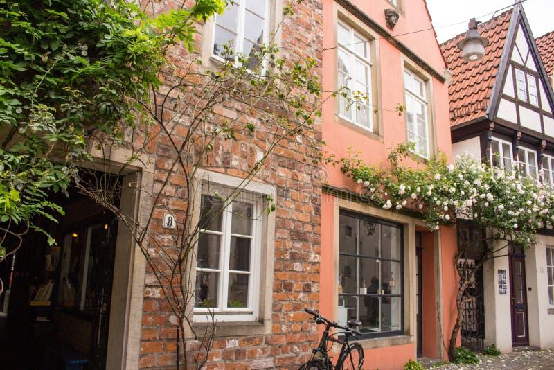 Calle en la ciudad vieja de Bremen con la decoración floral Edificios medievales con las rosas en la pared Arquitectura antigua e imagenes de archivo