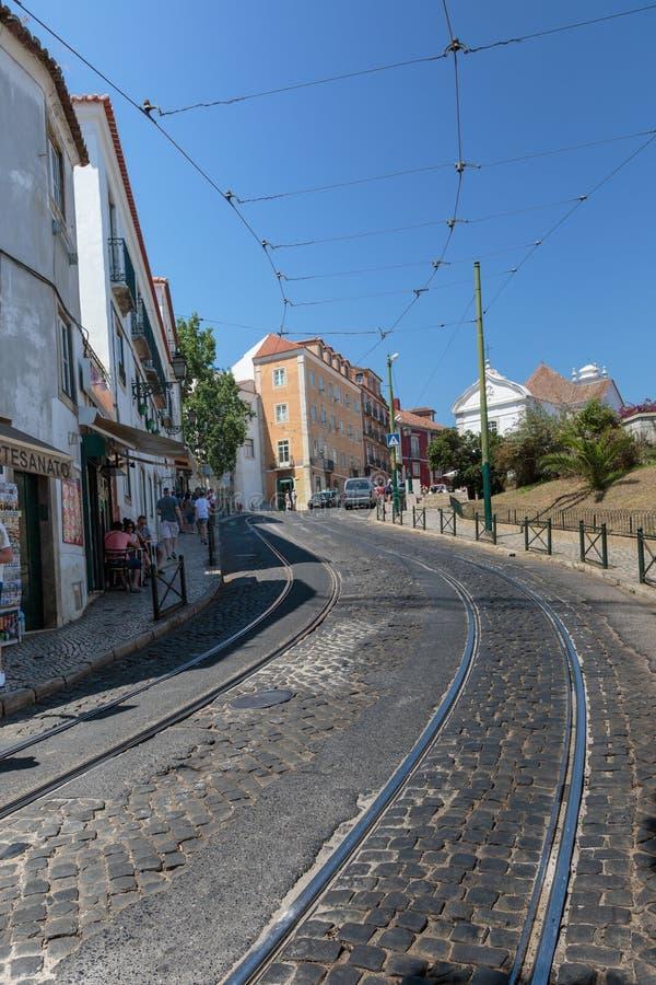 Calle en Lisboa con las pistas y los cables para el transporte de la tranvía, Portugal foto de archivo