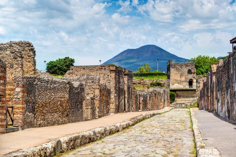 Calle en Pompeya que pasa por alto el Vesuvio, Italia imagen de archivo