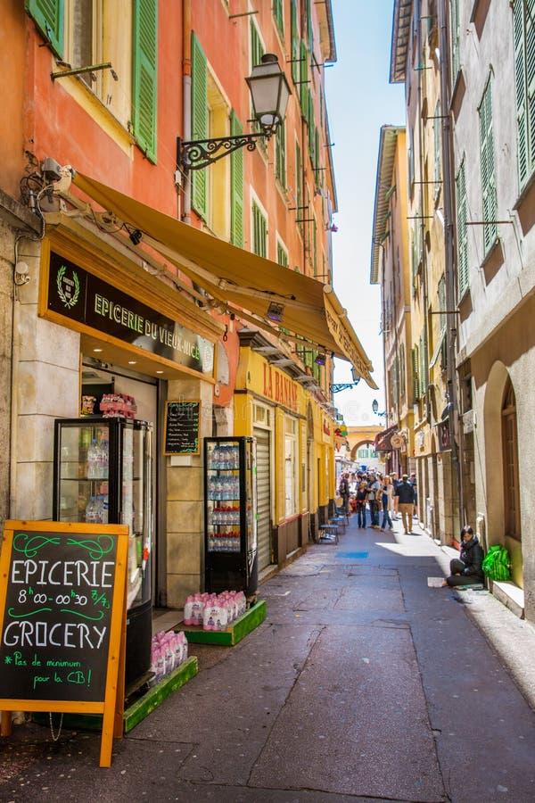 Calle estrecha colorida en Niza, francesa riviera Tiendas de souvenirs y turists imágenes de archivo libres de regalías