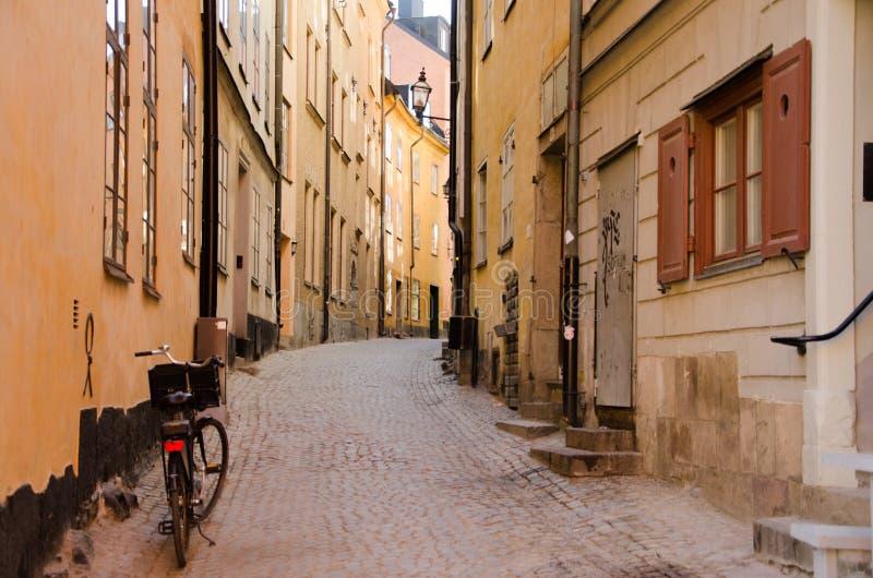 Calle estrecha con la bicicleta en la ciudad vieja del área stan de Gamla de Estocolmo, Suecia fotografía de archivo libre de regalías