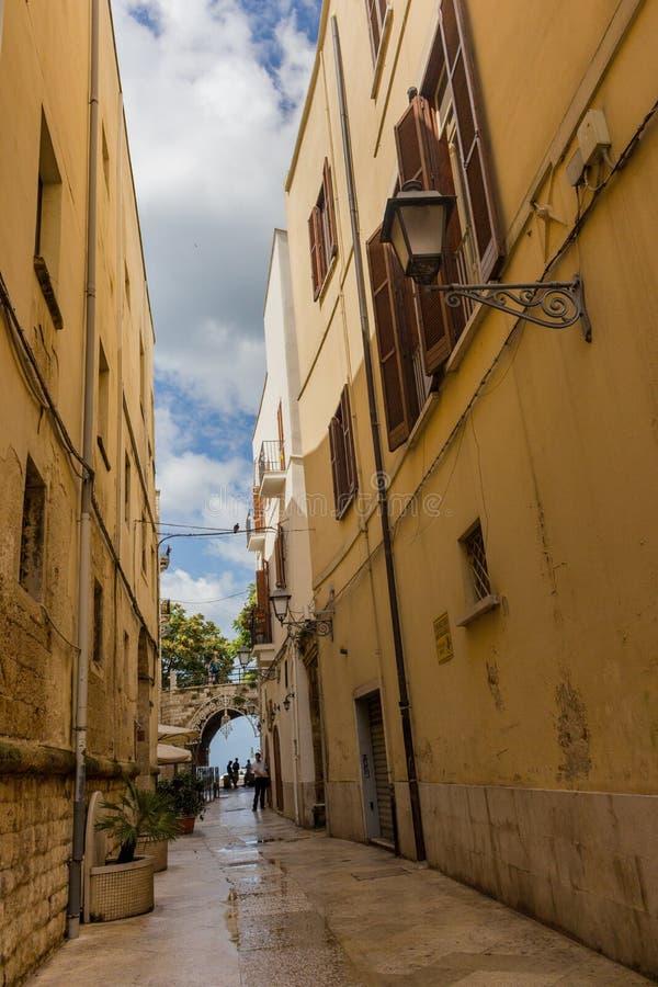 Calle estrecha con la linterna y arco en Bari, Italia Señal del sur italiana Arquitectura europea antigua Paisaje urbano mediterr imágenes de archivo libres de regalías