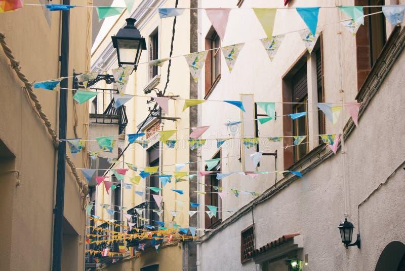 Calle estrecha con las fachadas amarillas de casas, de la linterna y de banderas decorativas en distrito histórico de la ciudad e fotografía de archivo