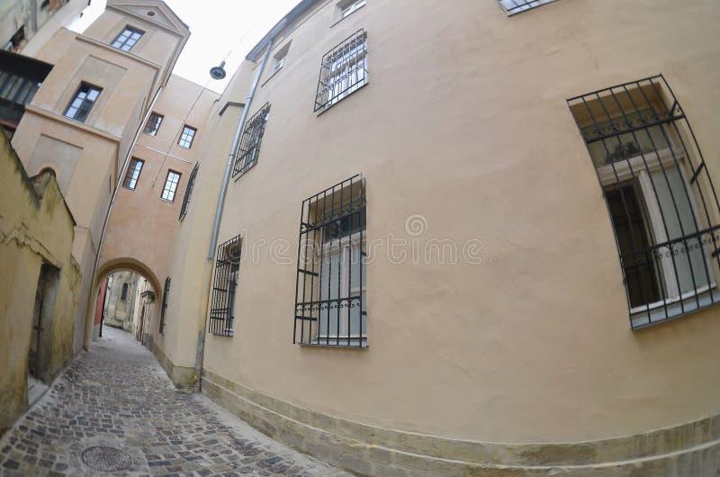 Calle estrecha con una trayectoria de las piedras de pavimentación Pase entre los edificios altos históricos viejos en Lviv, Ucra fotos de archivo