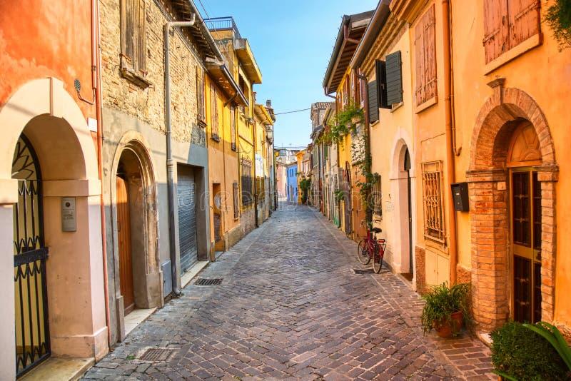 Calle estrecha del pueblo de los pescadores San Guiliano con las casas coloridas y una bicicleta en madrugada en R?mini, Italia imagenes de archivo