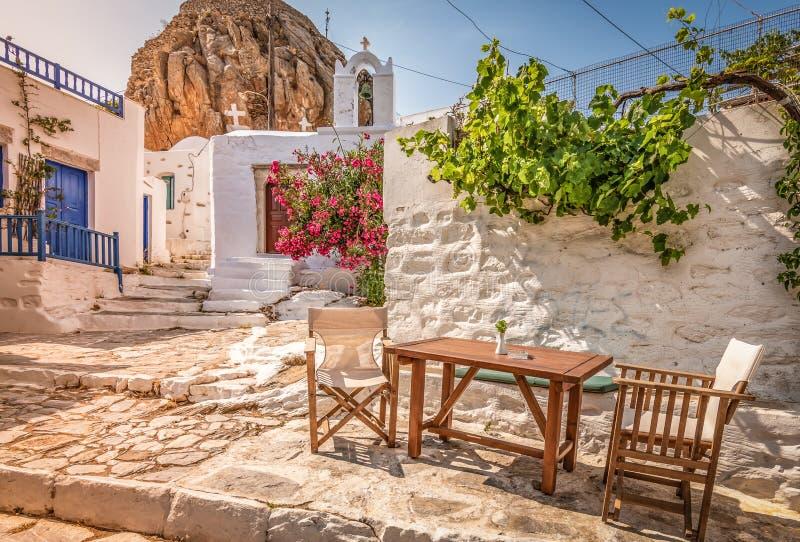 Calle griega tradicional en el centro de ciudad en el tiempo de la puesta del sol, isla de Amorgos, Grecia fotografía de archivo