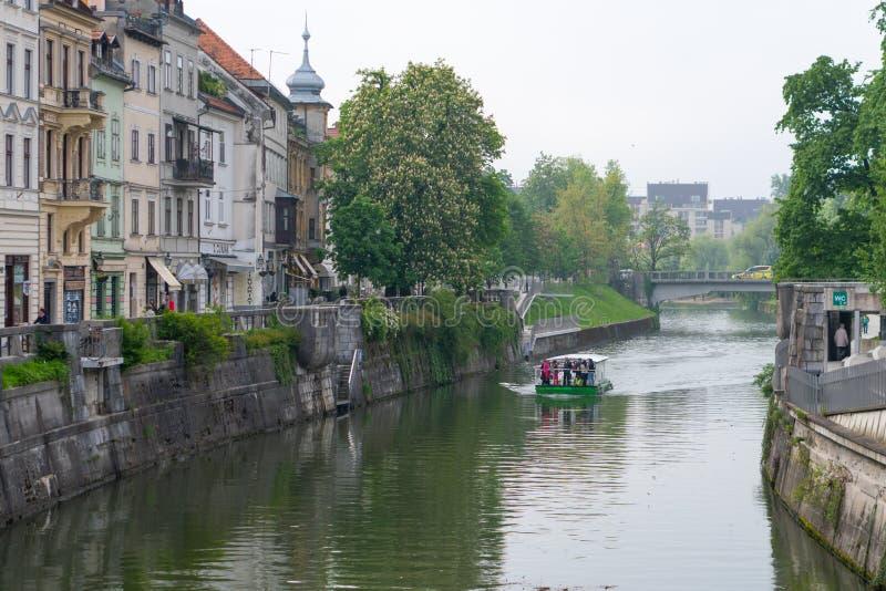 Calle hermosa en la ciudad vieja Eslovenia de Ljubljana Con el río Ljubljanica y el barco cruzándolo foto de archivo