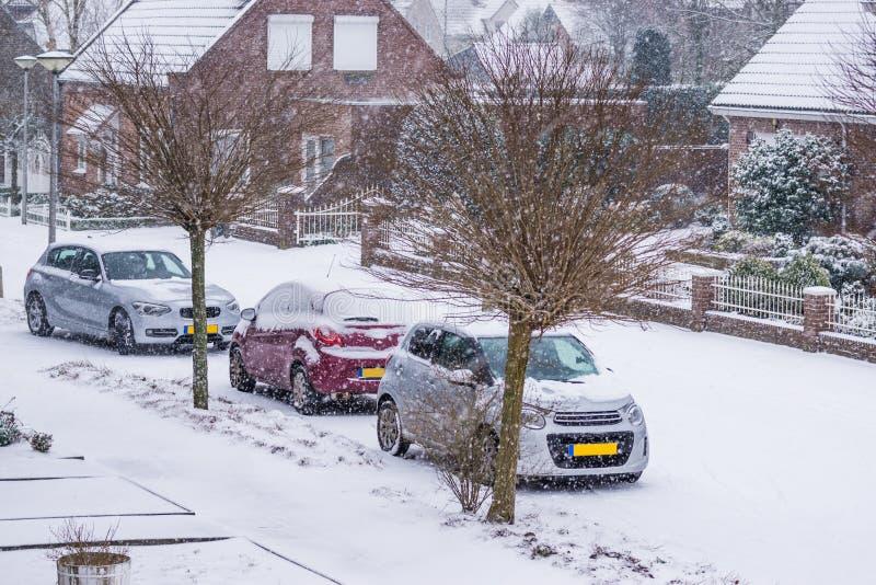 Calle holandesa con los coches parqueados cubiertos en nieve, un día del pueblo de invierno frío con el tiempo nevoso en los País imagen de archivo libre de regalías