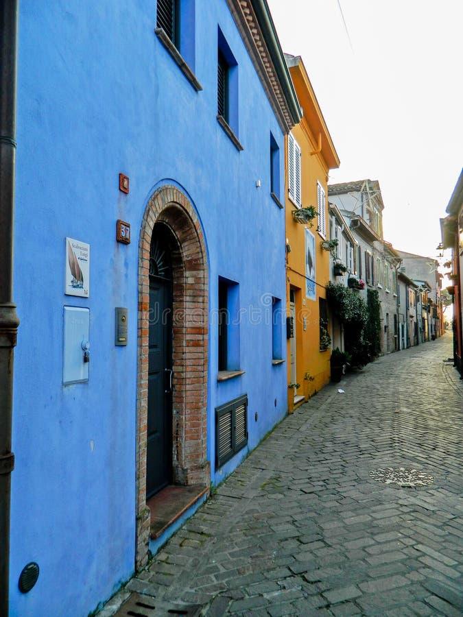 Calle italiana en la ciudad vieja, Rímini, Italia europa Escondrijos y grietas en el Rímini Callejón estrecho con los edificios v fotografía de archivo