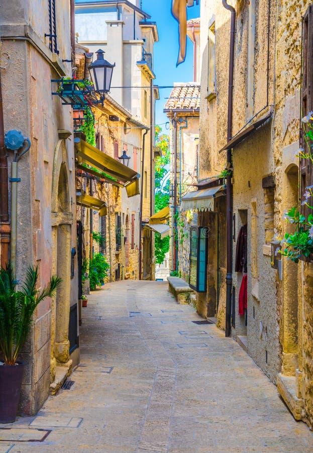 Calle italiana típica del guijarro con los edificios tradicionales y casas con las plantas verdes en las paredes en San Marino foto de archivo libre de regalías