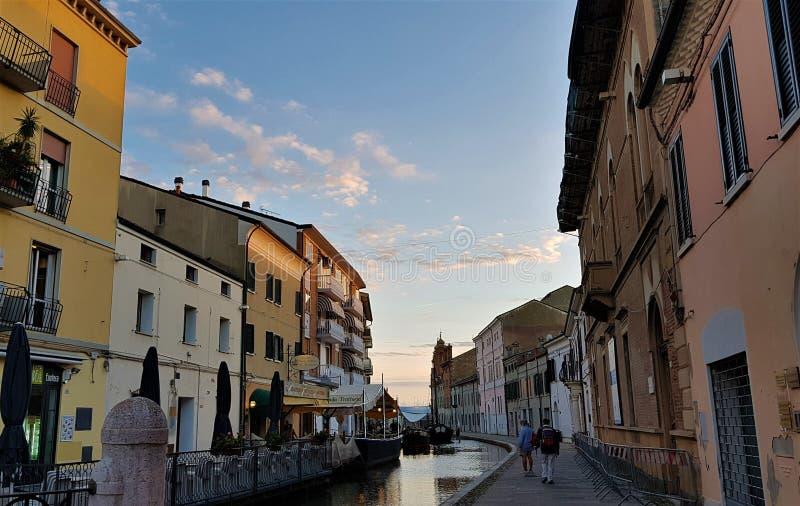 Calle a lo largo del canal en la ciudad vieja de Comacchio, Emilia Romagna, Italia imagenes de archivo