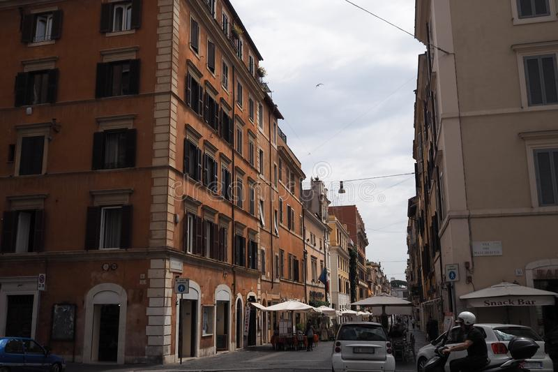Calle muy transitada con los coches y los restaurantes en Roma fotografía de archivo