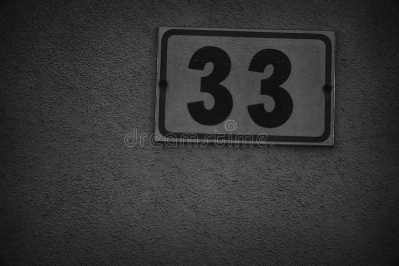 Calle número 33 en la pared beige, el fondo para el sitio web o los dispositivos móviles foto de archivo