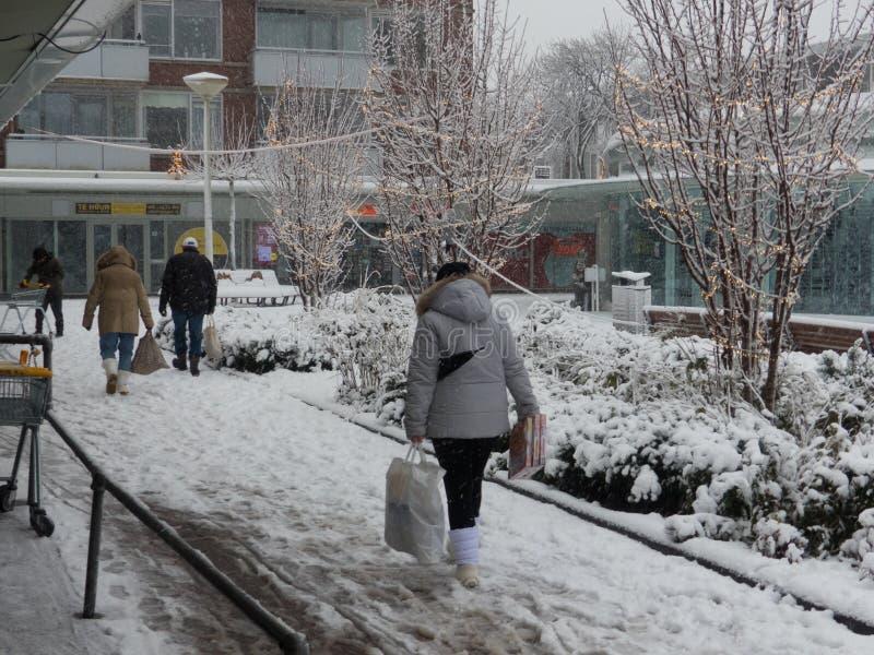 Calle nevada cerca del centro comercial con la gente que camina en las trayectorias resbaladizas afuera imágenes de archivo libres de regalías