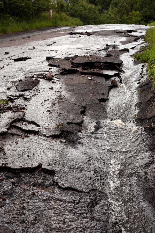 Calle pavimentada de la ciudad destruida después de tormenta y de la inundación fotos de archivo