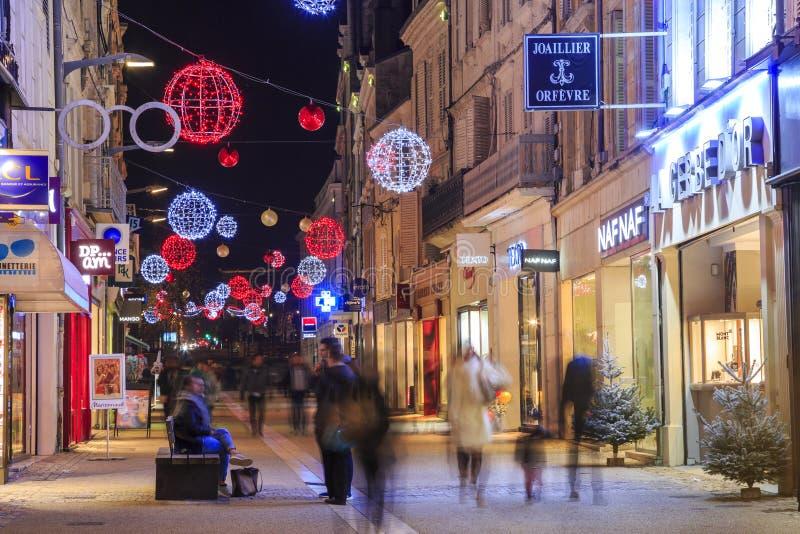 Calle peatonal iluminada por la decoración y las tiendas numerosas de la Navidad en cada lado imagen de archivo libre de regalías