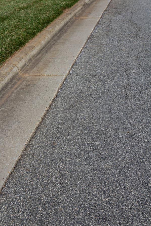 Calle residencial del asfalto con el encintado y la hierba verde concretos formados fotos de archivo