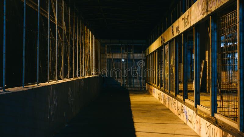 Calle sucia oscura del Grunge con la cerca atada con alambre y las luces amarillas de la ciudad que se escapan a través de lados  fotografía de archivo libre de regalías