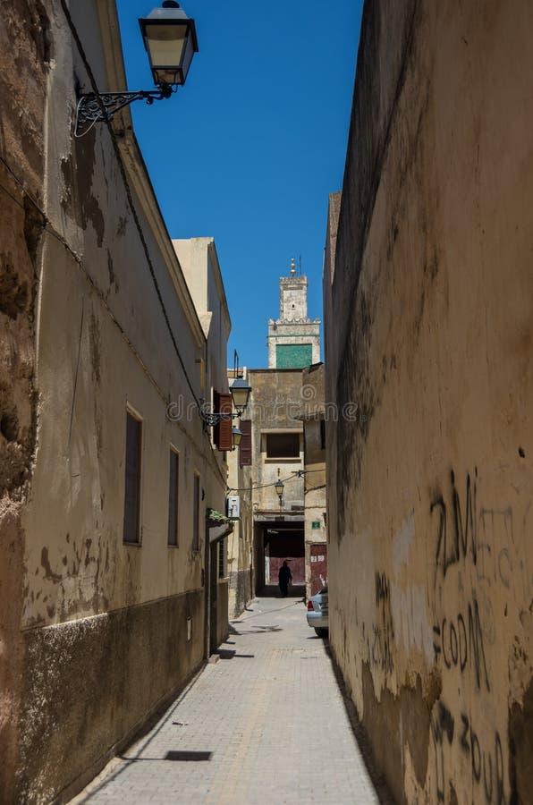 Calle típica estrecha de Meknes con el alminar de Madrasa Bou Inan foto de archivo