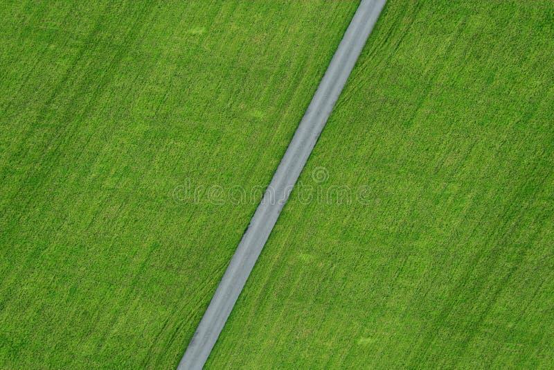 Calle vacía con el primer del campo del prado del verde de la opinión del ariel fotografía de archivo
