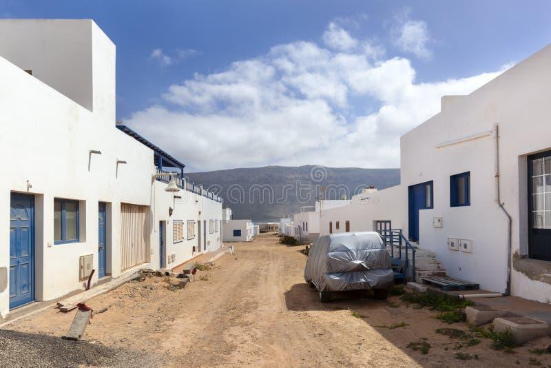 Calle vac?a con la arena y casas blancas en Caleta de Sebo en el La Graciosa de la isla foto de archivo libre de regalías