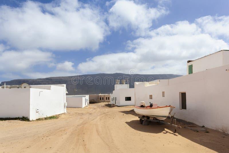 Calle vac?a con la arena y casas blancas en Caleta de Sebo en el La Graciosa de la isla imágenes de archivo libres de regalías