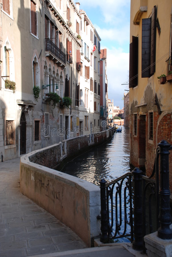Calle Veneziana. View of a Calle in Venice with boats and handrail in a sunny day - Venice, Italy royalty free stock images