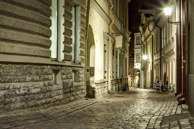 Calle vieja estrecha de la ciudad de Tallinn, Estonia en la noche piedra foto de archivo