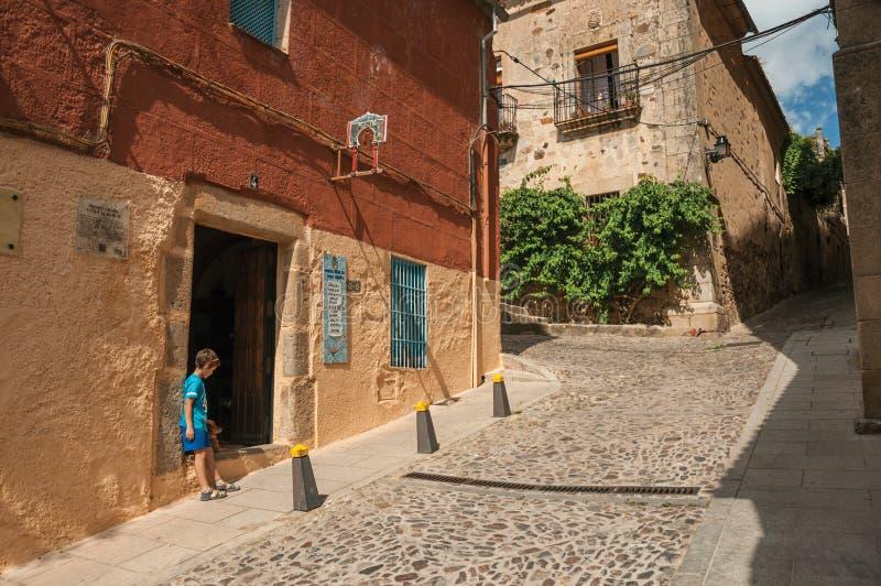 Callejón con el edificio viejo y muchacho al lado de la puerta abierta en Caceres fotos de archivo