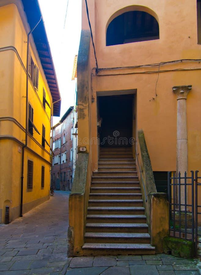 Callejón estrecho con el edificio histórico con la escalera y la puerta foto de archivo libre de regalías