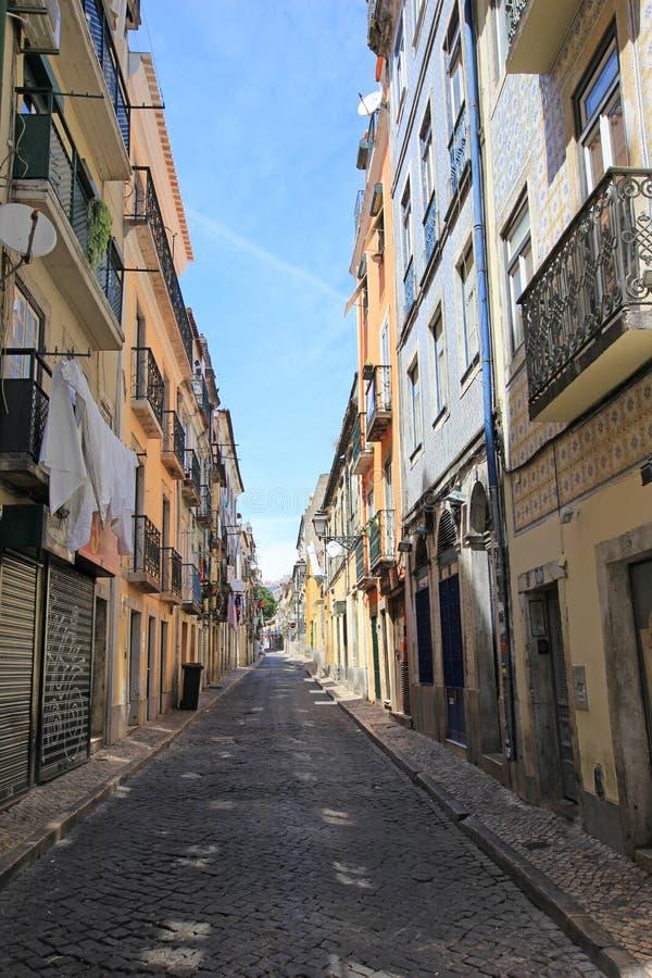 Callejón estrecho en la ciudad vieja del alto histórico del bairro en Lisboa, Portugal foto de archivo