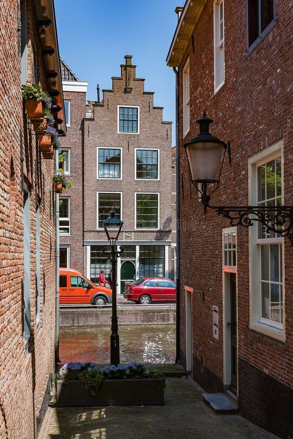Callejón típico en Alkmaar Países Bajos con la visión en el canal y la casa del canal imágenes de archivo libres de regalías