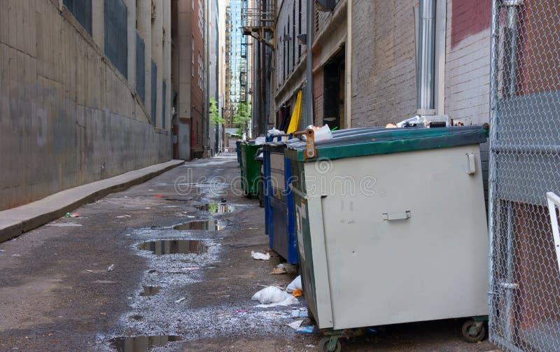 Callejón trasero asqueroso sucio con los contenedores y la basura fotografía de archivo