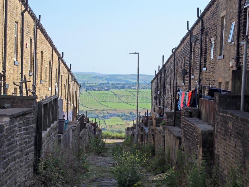 Callejón trasero septentrional típico en West Yorkshire con las yardas y las líneas que se lavan entre las calles de casas viejas imagenes de archivo