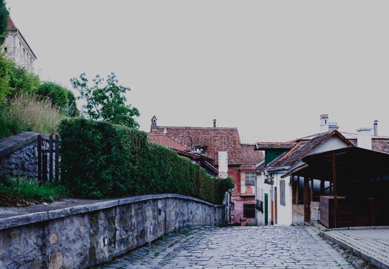 Calles de la ciudad medieval de Sighisoara, Rumania Edificios y cafés antiguos de la calle foto de archivo