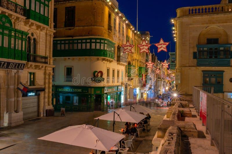 Calles hermosas del estrecho de La Valeta de la noche con la gente que va abajo de los edificios clásicos foto de archivo