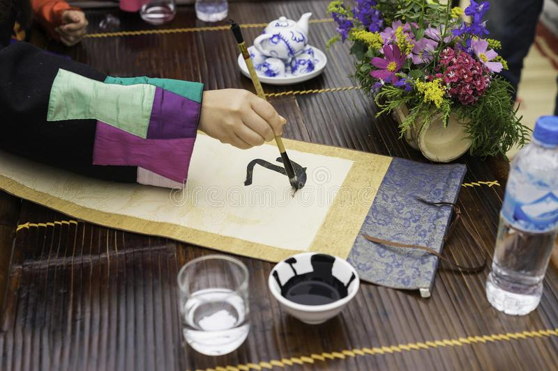 Calligrapher painting words on paper. Calligraphy is a traditional culture in Eastern lunar new year. Focus on the text stock image