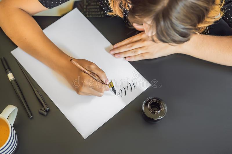 Calligrapher Young Woman writes phrase on white paper. Inscribing ornamental decorated letters. Calligraphy, graphic royalty free stock images