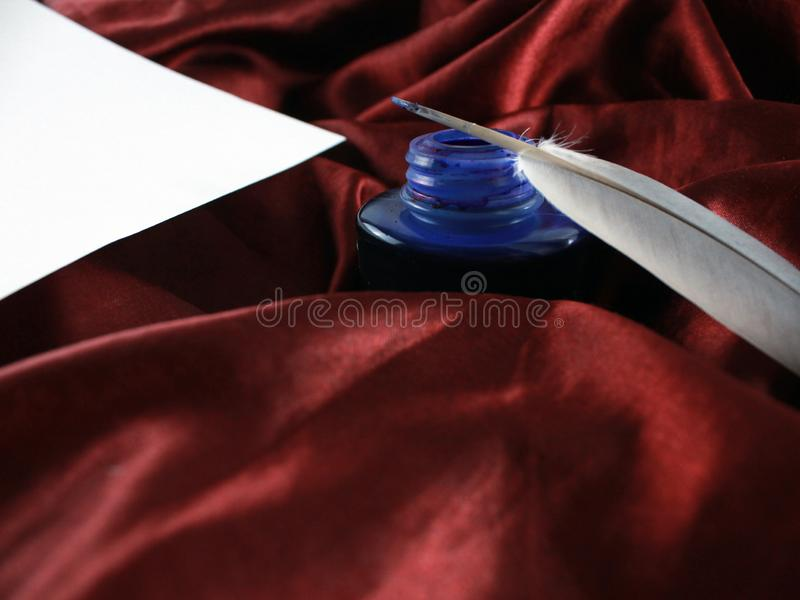 Calligraphic Quill on red silk satin fabric with white paper for calligraphy stock image