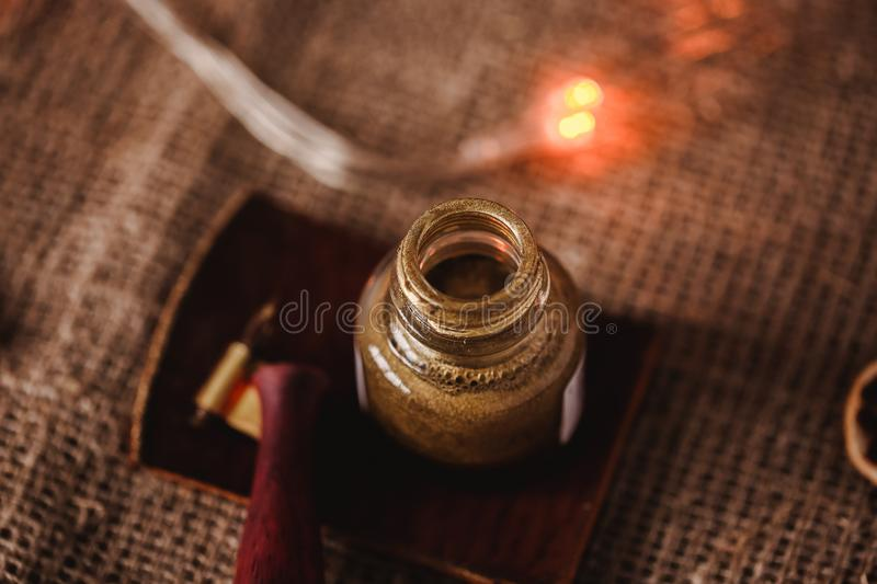 Calligraphic set. Calligraphy pen holder, pen and gold ink on vintage background with new year lights.  royalty free stock image