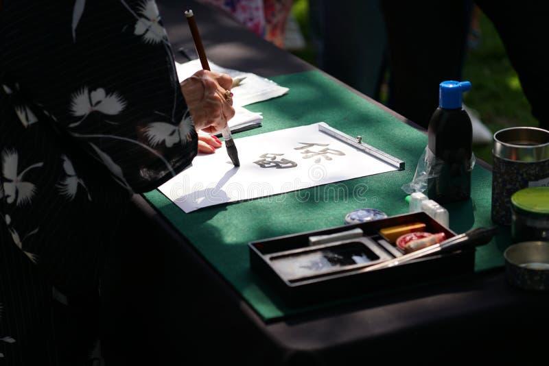 Calligraphie japonaise avec la brosse d'encre sur le papier image libre de droits